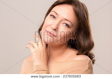 Charming Brunette Gently Touching Her Face And Oising On Camera. Beauty Concept. Mid Age Woman Over