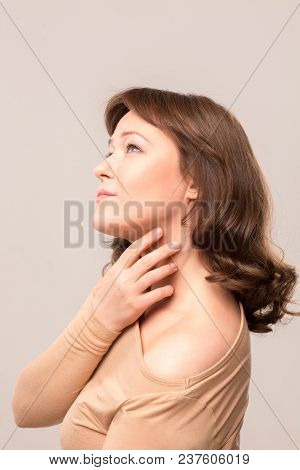 Side View Image Of Awesome Woman Looking Up And Touching Her Neck. Beauty Concept. Mid Age Woman Ove