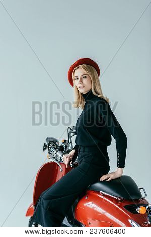 Smiling Blonde Girl In Black Clothes Posing By Red Motorcycle Isolated On Grey