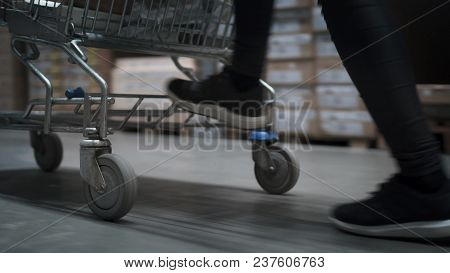 Closeup View On Woman's Feet Are Jumping On A Shopping Trolley In The Store. Female In Sneakers Is F