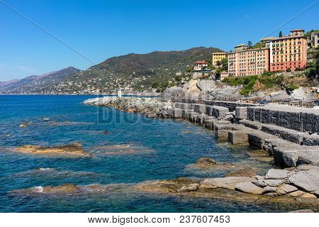 Wave breaker and colorful houses on background in Camogli - small town and popular resort on Mediterranean sea in Italy.