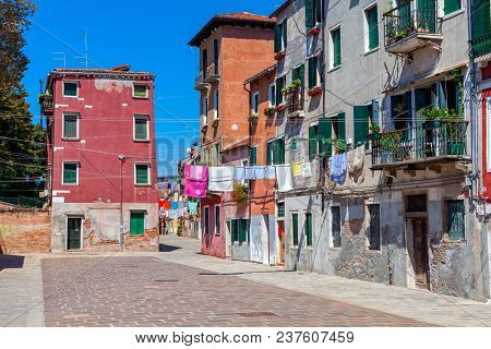 Laundry drying hung among old colorful houses on narrow street in Venice, Italy.