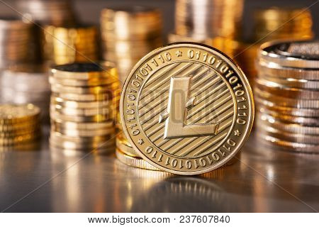 Coin Of The Crypto Currency Litecoin With Several Stacks Of Coins In The Background