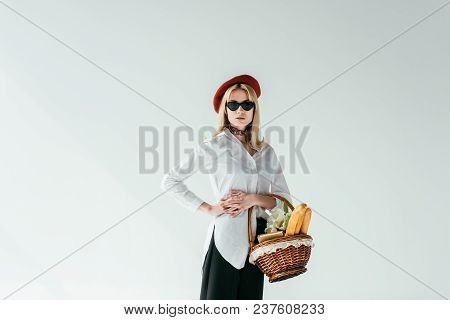 Stylish Blonde Girl Holding Basket With Bread And Flowers Isolated On Grey
