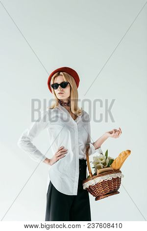 Stylish Pretty Woman Carrying Basket With Bread And Flowers Isolated On Grey