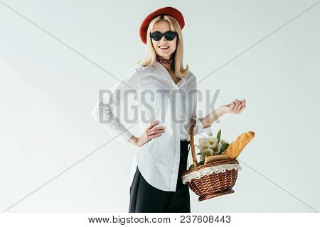 Smiling Blonde Girl Carrying Basket With Bread And Flowers Isolated On Grey