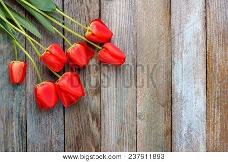 Bouquet Of Red Tulips On Wooden Retro Grunge Background With Copy Space. The Concept Of Mothers Day,