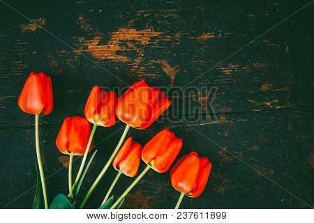 Bouquet Of Red Tulips On Black Wooden Retro Grunge Background With Copy Space. The Concept Of Mother