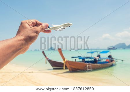 Hand Holding An Airplane With Longtail Boats, Beach And Blue Sea In Background.
