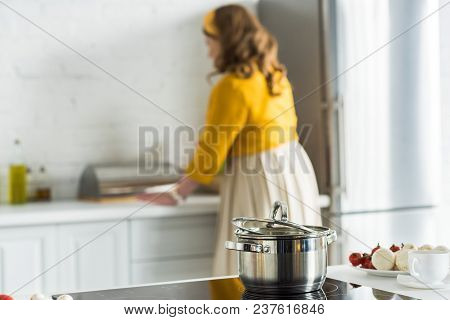 Woman Cooking In Kitchen With Pan On Electric Stove On Foreground