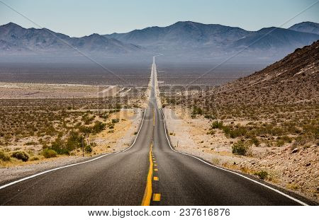 Classic Panorama View Of An Endless Straight Road Running Through The Barren Scenery Of The American