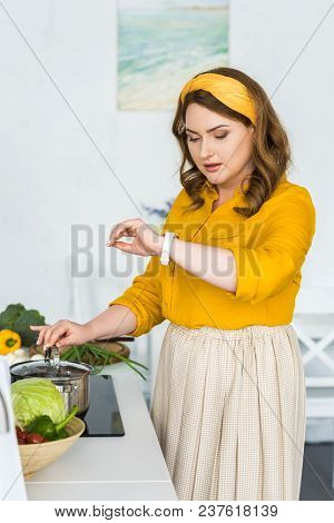 Beautiful Woman Checking Time On Wristwatch Near Pan On Electric Stove In Kitchen