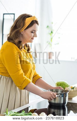 Side View Of Beautiful Woman Putting Pan On Electric Stove In Kitchen