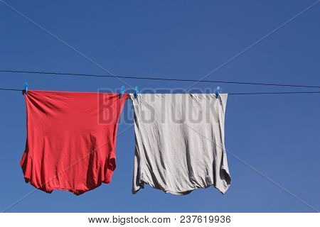 Red And Grey T-shirts On Clothes Line With Blue Sky Copy Space.
