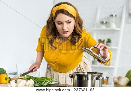 Beautiful Woman Cutting Vegetables And Looking Into Pan On Electric Stove In Kitchen