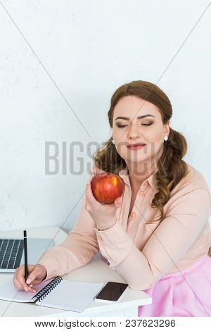 Beautiful Woman Looking At Apple In Kitchen