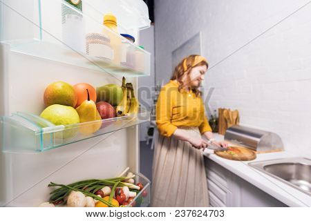 Beautiful Woman Cutting Vegetables At Kitchen With Fridge On Foreground