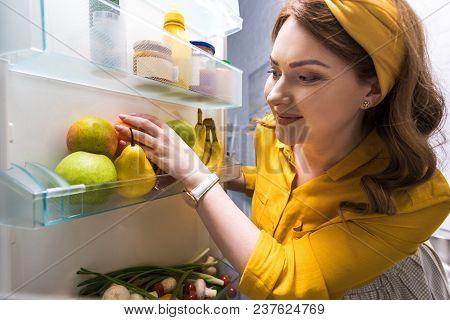 Beautiful Woman Taking Fruits From Fridge At Kitchen