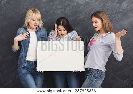 Three Surprised Girls Holding Blank White Banner With Copy Space For Advertisement On Gray Studio Ba