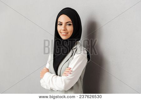 Portrait of a smiling young arabian woman standing with arms folded and looking at camera isolated over gray background