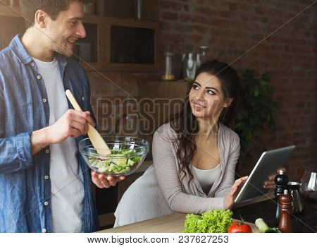 Happy Couple Preparing Dinner With Recipe, Using Tablet In Their Loft Kitchen At Home. Preparing Veg