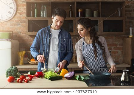 Happy Couple Cooking Healthy Dinner Together In Their Loft Kitchen At Home. Preparing Vegetable Sala