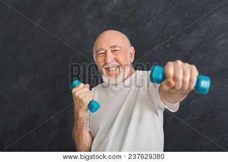 Senior Fitness Man Training With Dumbbells At Gym, Doing Strength Exercise For Biceps, Black Backgro