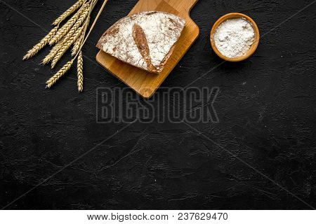 Appetizing Fresh Bread Concept. Sliced Loaf Near Ears Of Wheat On Black Background Top View.
