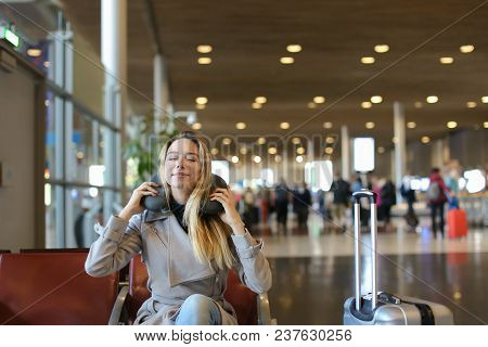 Female Person Sitting With Neck Pillow And Luggage In Airport Waiting Room. Concept Of Traveling Abr