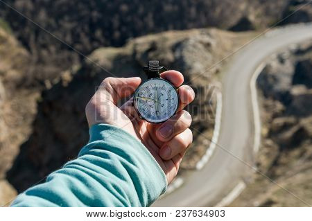 Close-up A Man's Hand Holds A Pocket Compass Against The Backdrop Of A Mountain Road And Forest. The