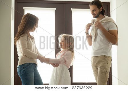 Caring Mother Helping Little Daughter Dressing For Walk With Dad, Family Talking Getting Ready To Go
