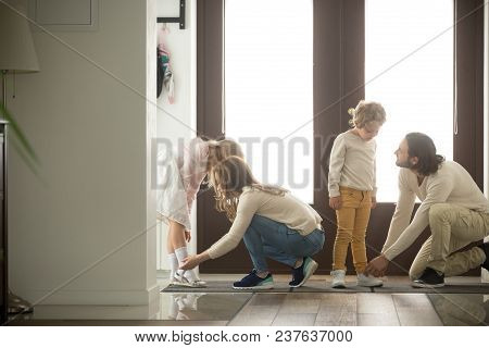 Parents Helping Children Son And Daughter Put Shoes On Or Take Off In Hall Getting Ready To Go Out T