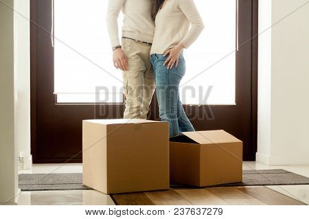 Happy Couple Embracing Standing Near Cardboard Boxes On Moving Day, Homeowners Renters Tenants Just