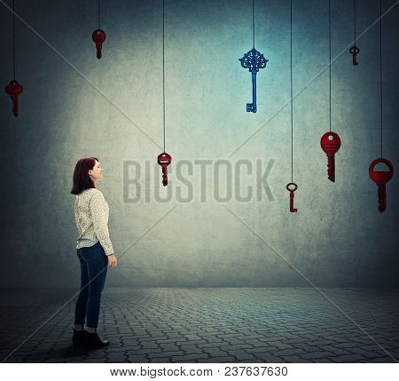Smiling Woman Standing In Front Of Suspended Glowing Keys, Try To Choose One Different Of Others. Co