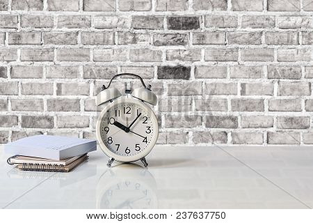 White Alarm Clock And Notebook On White Table With Brick Wall