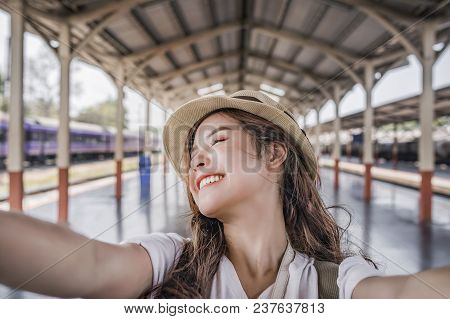 Close-up Selfie-portrait Of Attractive Girl With Long Hair Standing At Railway Statioin. She Is Smil