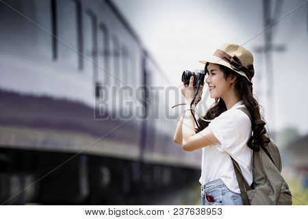 Young Beautiful Woman Traveler With Backpack Holding Vitage Camera And Taking Photos A Train At Rail