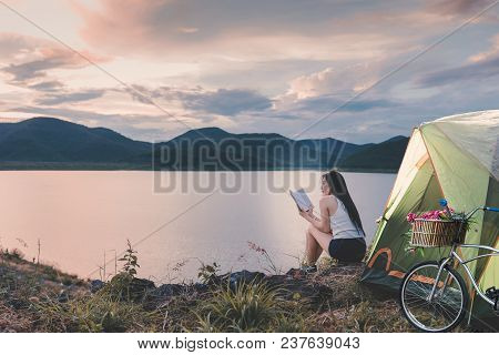 Young Woman Sitting Near The Lake And Reading A Book While Tenting Outdoor On Vacation.