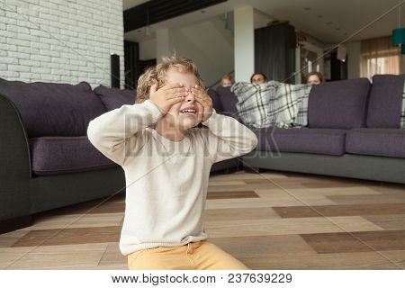 Kid Boy Playing Hide And Seek Game At Home, Child Closing Eyes With Hands Counting While Parents And