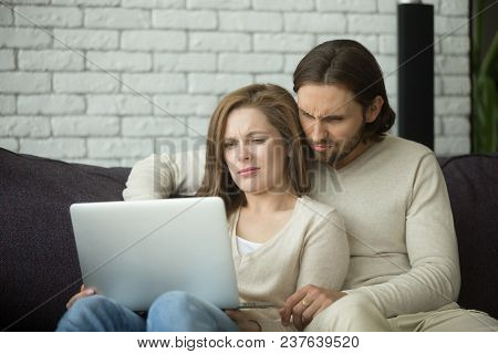 Young Couple Looking On Laptop Feeling Confused By Reading Online News Browsing Internet, Annoyed Ma