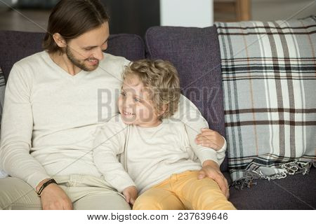 Happy Young Father Embracing Kid Sitting On Sofa, Loving Caring Dad Hugging Little Boy Having Fun To
