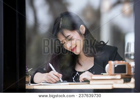 Young Beautiful Woman Smiling And Holding Pen  Pointing On The Book While Sitting At Coffee Shop