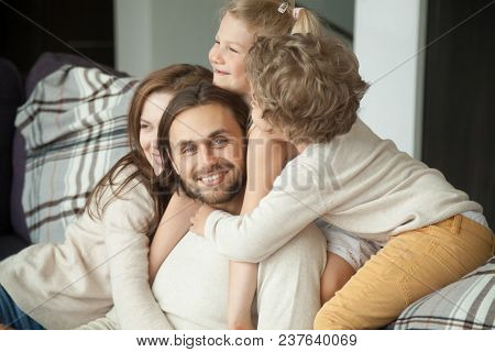 Smiling Man Looking At Camera Enjoying Kids And Wife Embracing Dad, Happy Loving Family Parents And