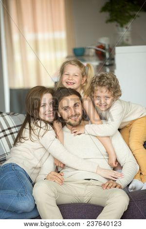 Happy Beautiful Family With Children Sitting On Sofa Embracing Looking At Camera, Cheerful Young Cou