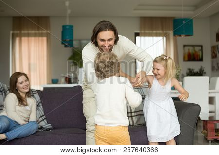 Happy Young Dad Having Fun With Kids At Home, Smiling Daddy Playing With Children Son And Daughter I