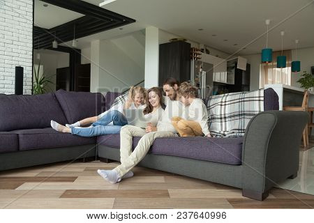 Smiling Parents With Kids Having Fun With Laptop In Cozy Living Room Interior, Couple With Children