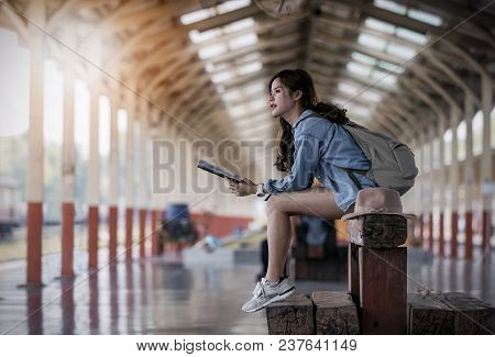 Young Woman Traveler In Blue Jeans Holding Book An D Sitting On Wooden Bench At Platform Of Railway