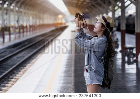Young Beautiful Woman Traveler With Backpack Holding Vitage Camera And Taking Photos  At Railway Sta