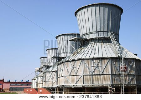 Large Gray Cooling Towers For Cooling Circulating Water, Standing In A Row At An Oil Refinery, Petro
