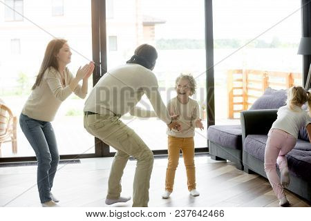 Happy Family With Excited Children Playing Hide And Seek Active Game Indoor, Blindfolded Father Catc